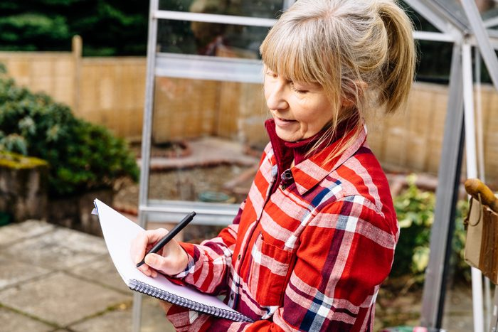 woman writing on note pad in the garden to plan for next season
