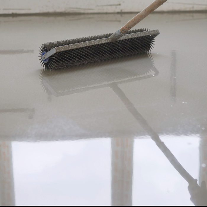 Leveling the floors with a cement mixture. Needle roller for self-leveling floor. Epoxy concept. concrete floor. on the horizon. close-up. needle roller to remove air bubbles. there is toning. then there will be painting. Needle roller for self-leveling