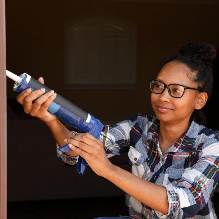 Caulking Gun African American Woman Glasses Horizontal