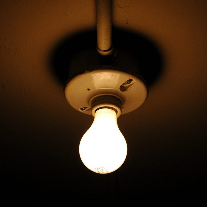 exposed light bulb on ceiling in dark closet at home