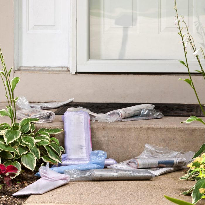 newspapers piling up on the front steps of a home