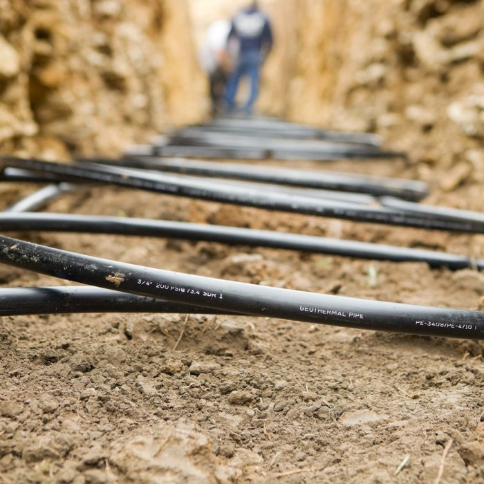 Workers Laying Geothermal Coils In An Underground Trench