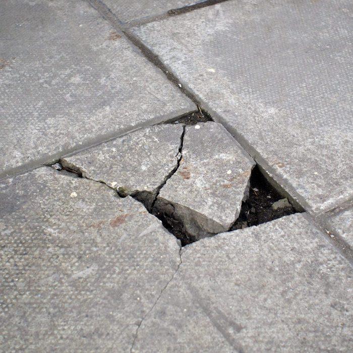A dangerous broken paving slab on a pavement.
