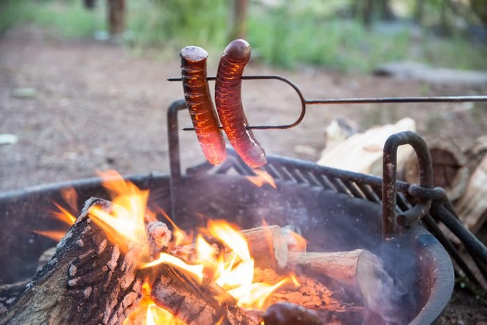 cooking hot dogs over a campfire