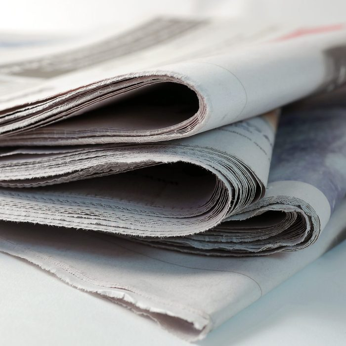four newspapers piled up