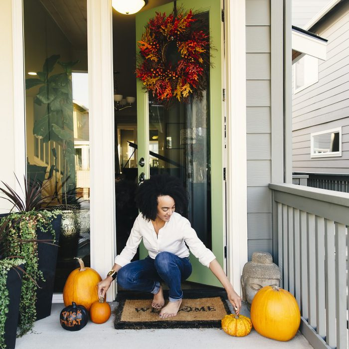 Mixed race woman arranging pumpkins on patio