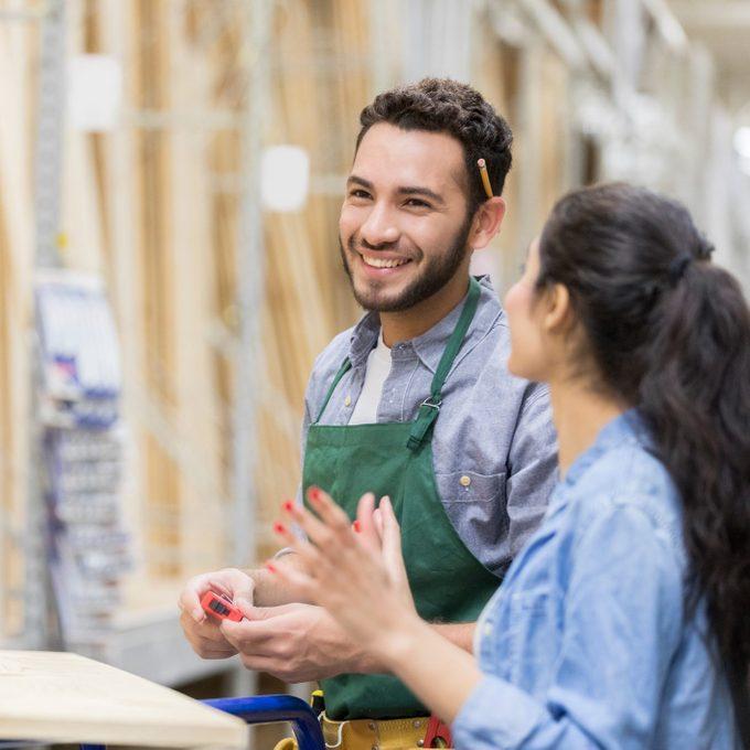 Cheerful lumber yard employee assists female customer