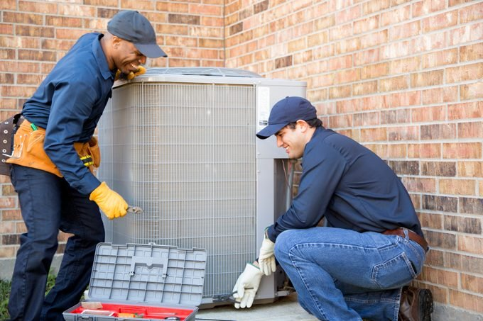 team of hvac installers repairing central air conditioning system outside of house
