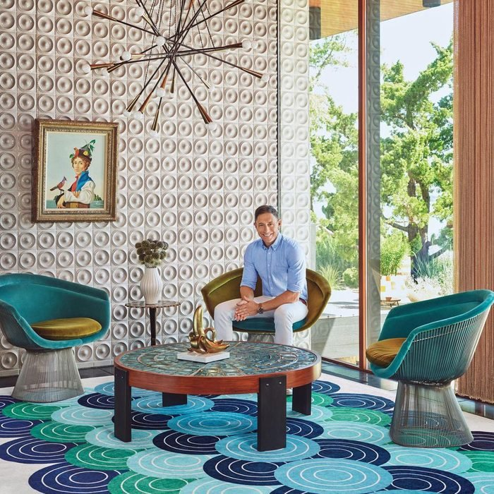 Jonathan Adler sitting in a decorated room with a Ruggable rug to announce the jonathan adler x ruggable collection