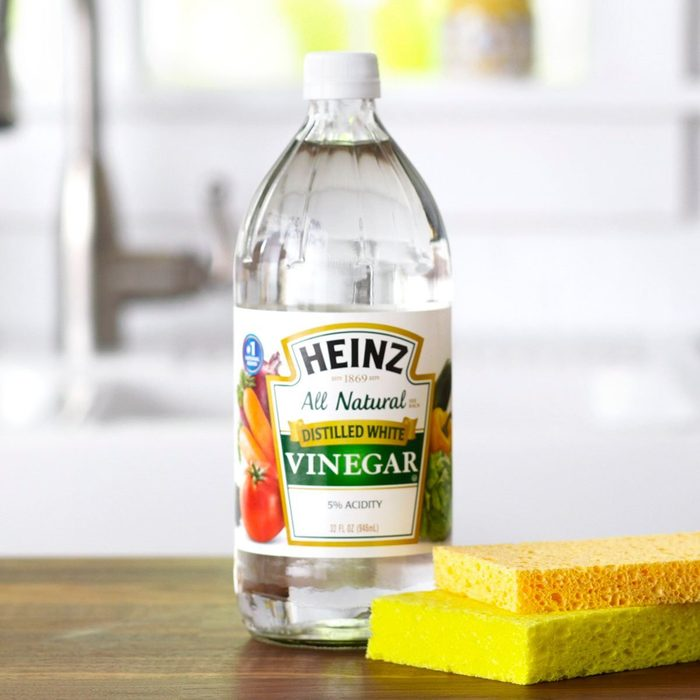 Vinegar and cleaning sponges on wooden surface
