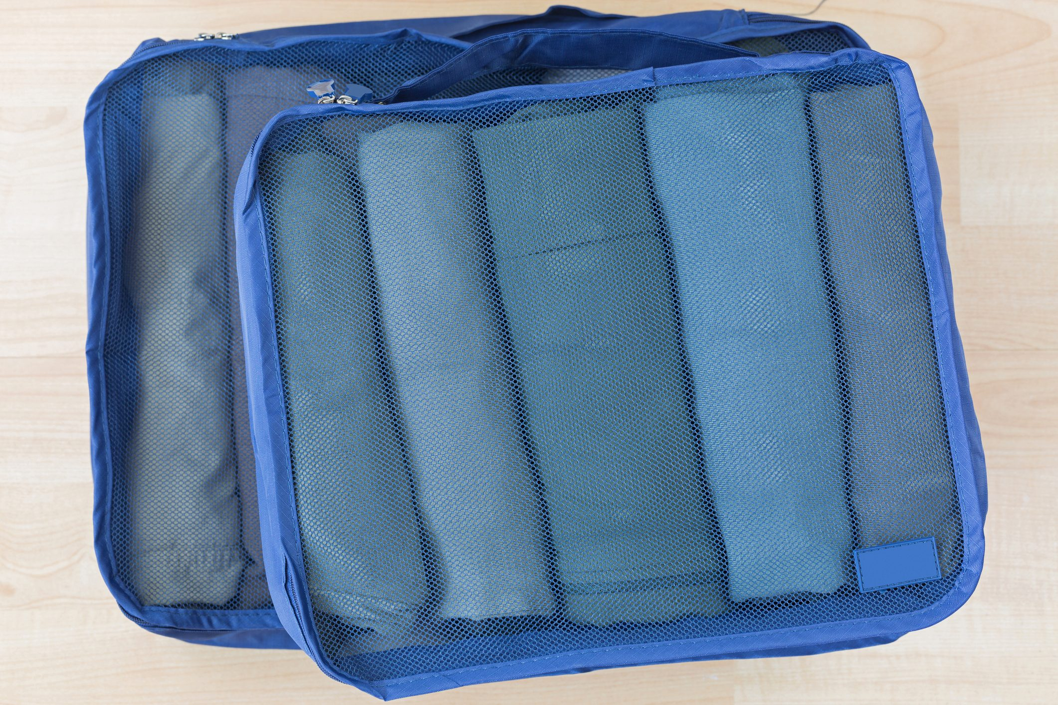 Cube Meshed Bags With Rolled Clothes. Set Of Travel Organizer To Help Packing Well Organized