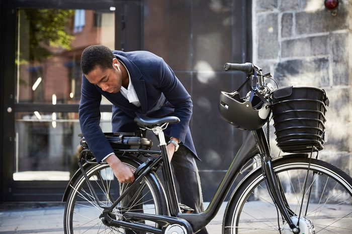 Young male commuter locking electric bicycle in front of building in city