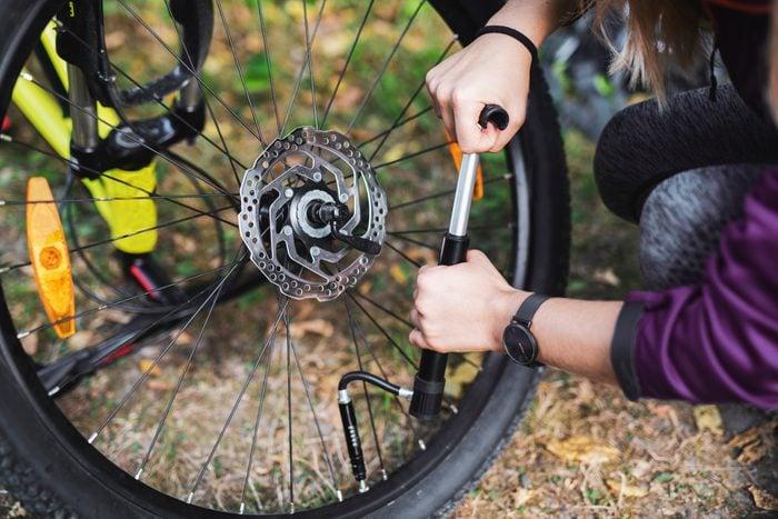 Woman repairing bicycle in nature.