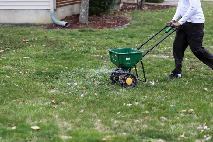 a man using a seed spreader on lawn