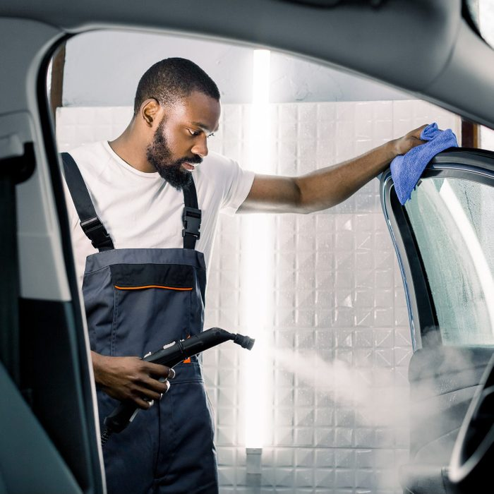Car detailing, steam cleaning concept. Handsome African man in overalls and t-shirt, worker of car wash center, cleaning car with hot steam cleaner and blue microfiber cloth. Car detailing concept
