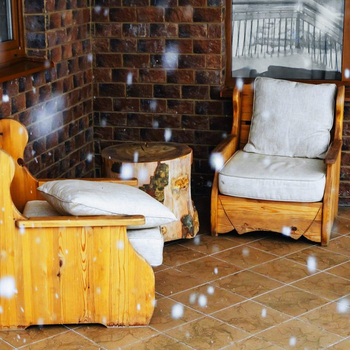 Wooden armchairs with cushions on a covered patio during a snowfall