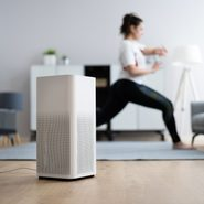 Young Woman Using Air Ionizer at home while she does yoga in the background
