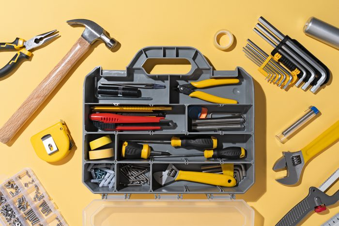 Opened DIY Toolbox With a Collection of Tools on a yellow background