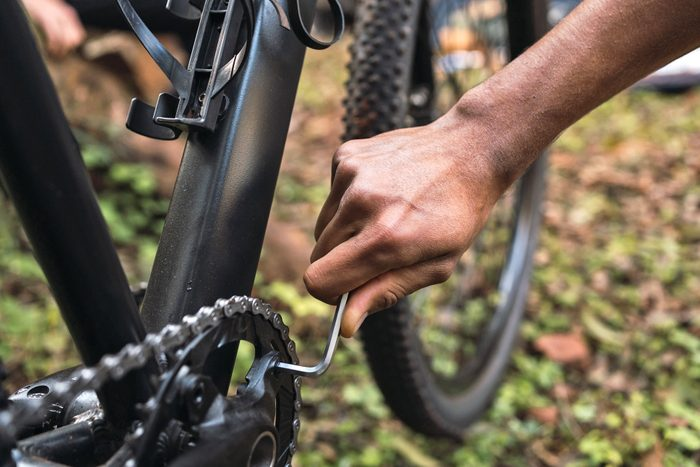 man using allen wrench to fix his bike