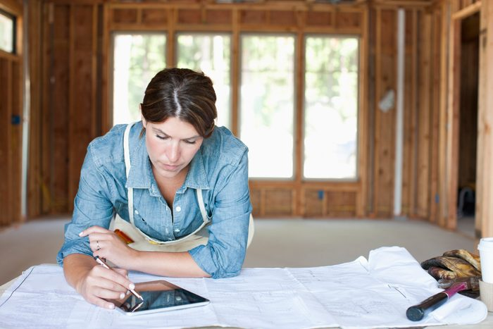 female construction professional using digital tablet in unfinished room of house
