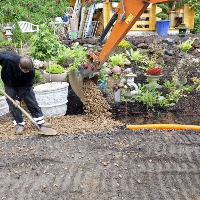 placing rocks and gravel over french drain pipe system