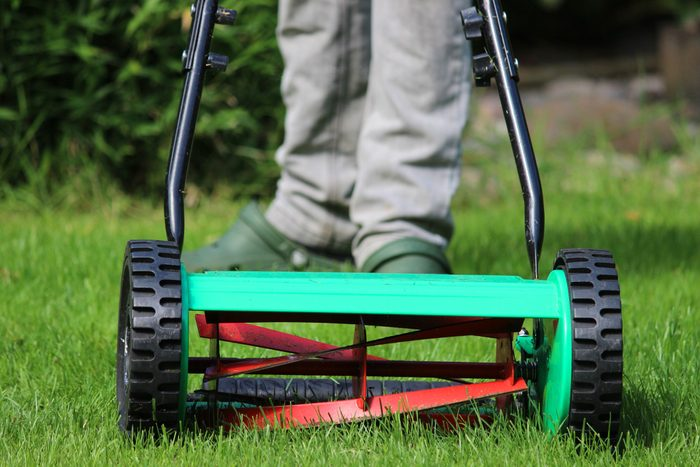 close up of person using a manual push lawn mower in back yard