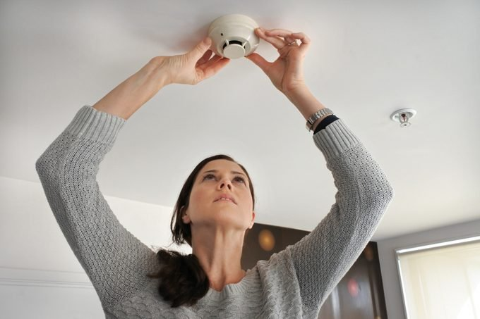 Woman checking smoke detector in home