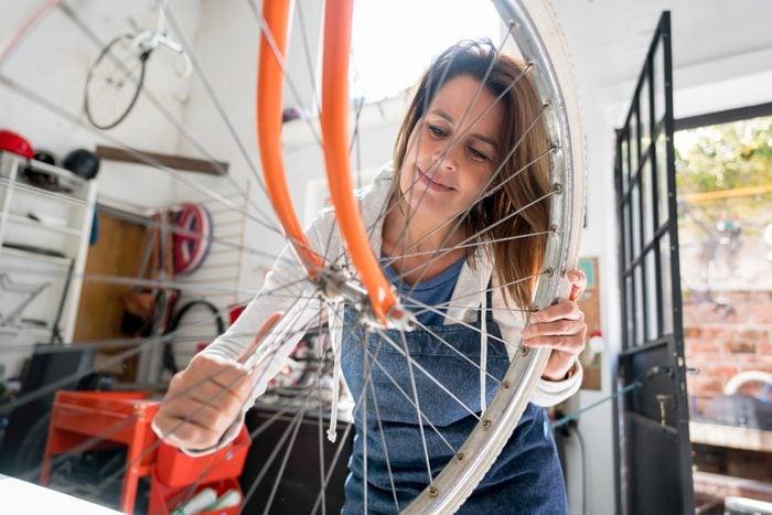 Woman fixing her bike in repair shop