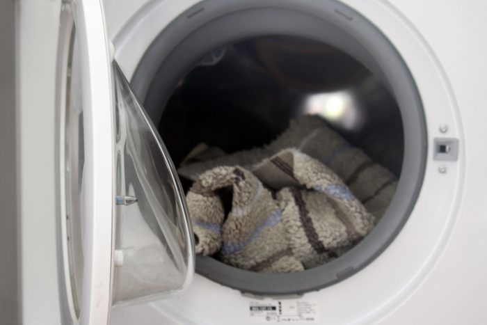 Washing Machine open with a gray bath mat in the drum