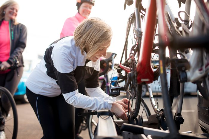 mature woman securing her bike to a bike rack on the back of a car