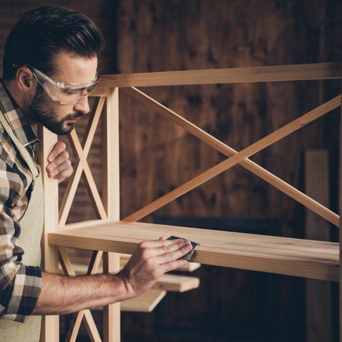 man building a bookshelf in garage