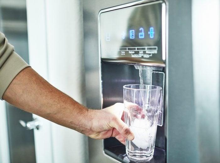 man dispensing water from refrigerator