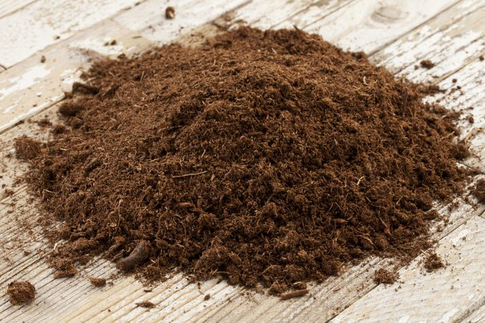 small pile of sphagnum peat moss soil conditioner for gardening on a wood surface